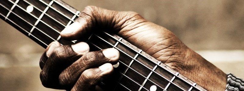 Une main sur les cordes de la guitare