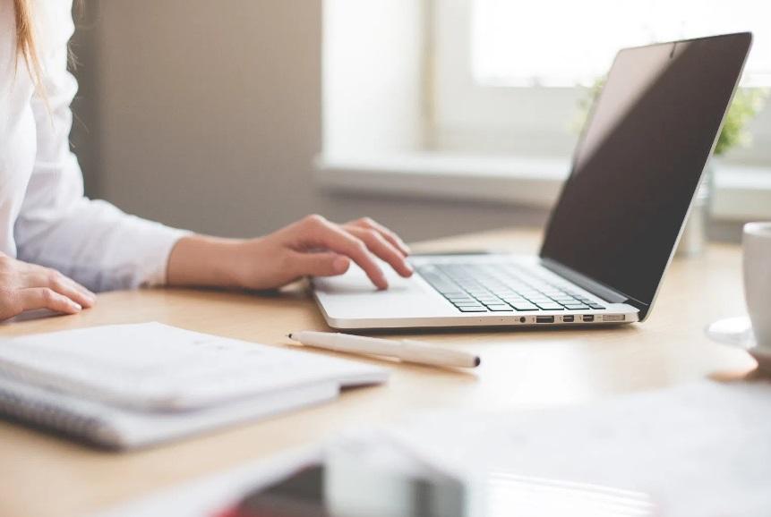 Femme devant un ordinateur gris
