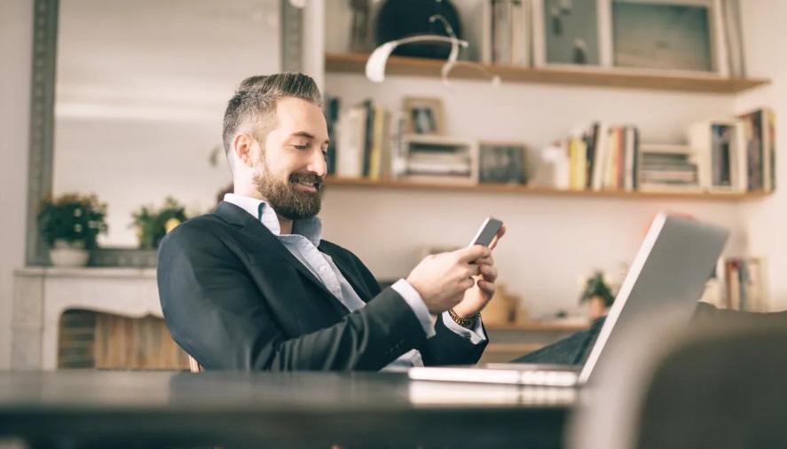 Homme sur un smartphone devant un ordinateur