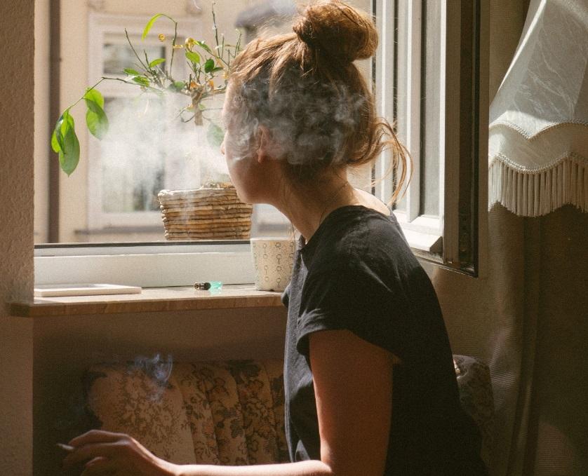 Femme à la fenêtre en train de fumer