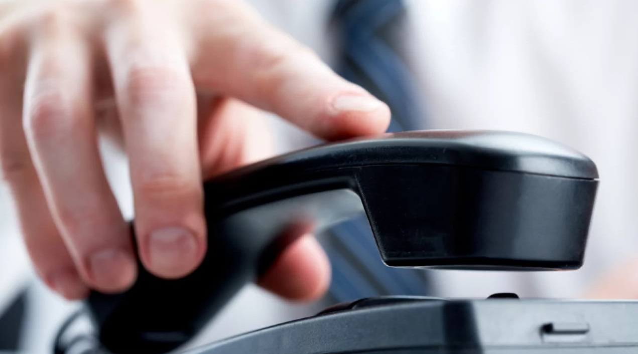 Une main qui tiens un téléphone fixe