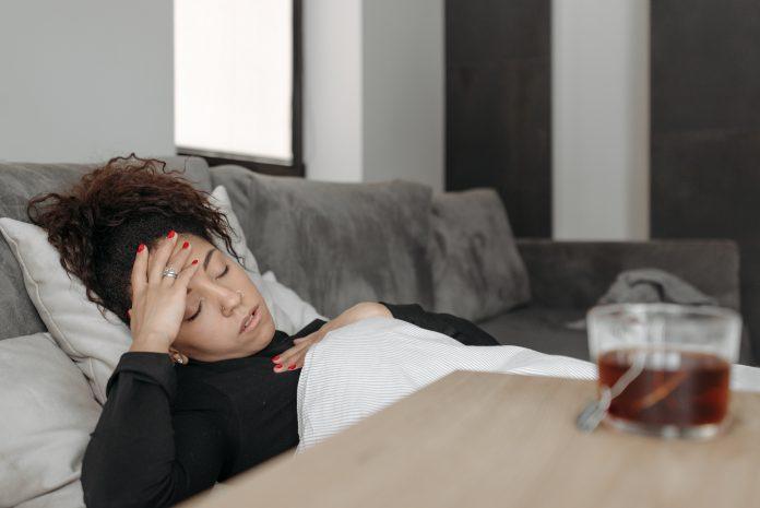 femme au mal de tête boit tisane comme remède naturel