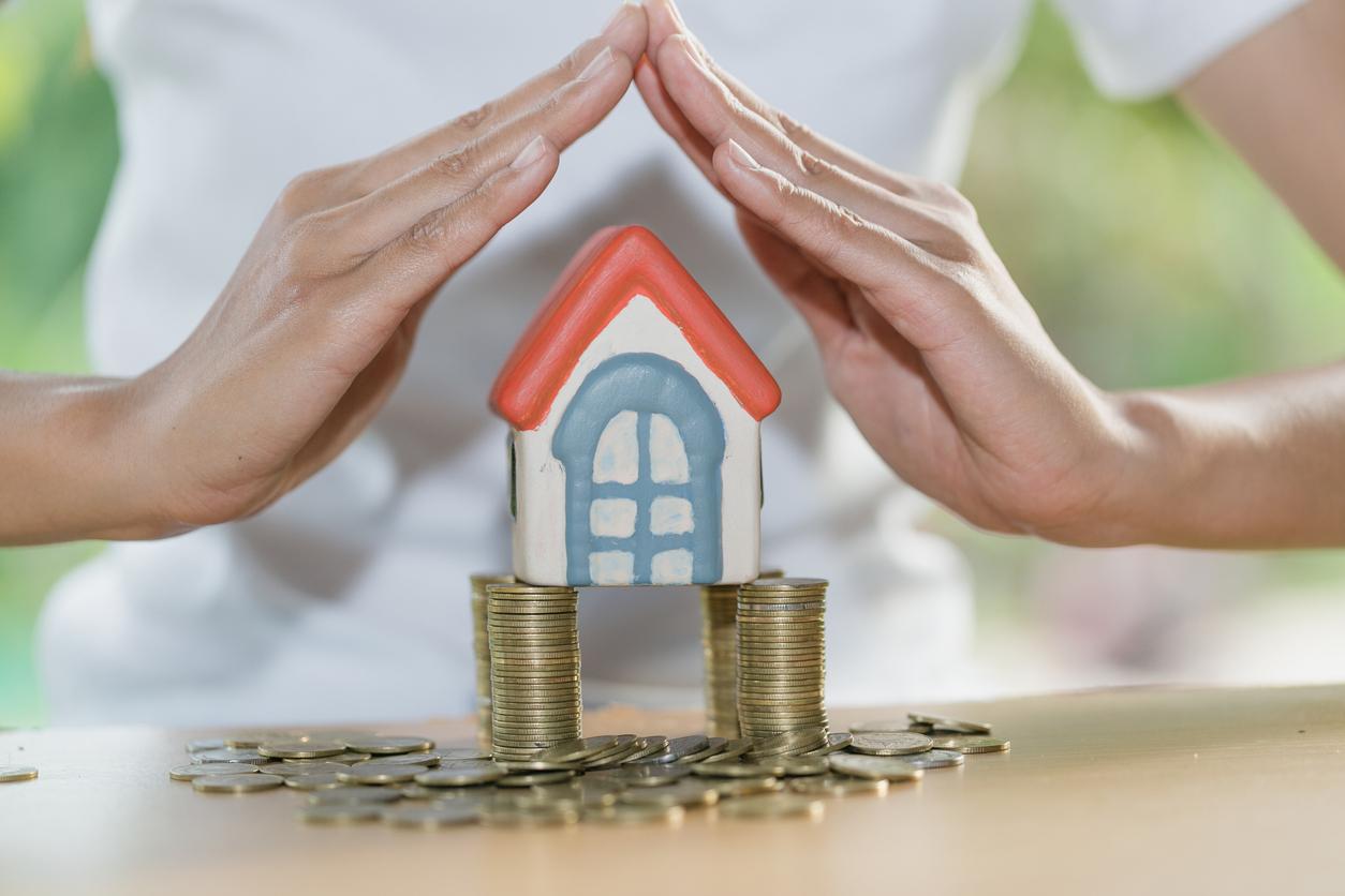 maison miniature sur pile pièce de monnaie